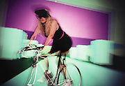 Cyberspace hi-cycle: Carolyn Hedrich pedals an exercise bike through a virtual, computer generated landscape, projected into her eyes through two video screens in her headset. Riders are encouraged to pedal as fast as they are capable, because, on reaching a certain pedal speed, the computer creates the impression of take-off and flight. Model Released (1990)