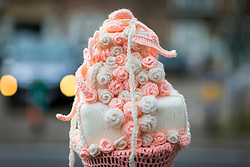 © Licensed to London News Pictures. 13/05/2018. Thirsk UK. Picture shows a woollen wedding cake. The Thirsk Yarn bombers have decorated the town centre of Thirsk in North Yorkshire this morning with Prince Harry & Megan Markle wedding related woollen creations to celebrate the upcoming royal wedding at the weekend. Photo credit: Andrew McCaren/LNP
