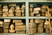 Moulds of various statues on shelves in the studio of the Stpathy family of idol makers, Swamimalai, India.The current Stpathy family is the twenty third generation of bronze casters dating back to the founding of the Chola Empire. The Stapathys had been sculptors of stone idols at the time of Rajaraja 1 (AD985-1014) but were called to Tanjore to learn bronze casting. Their methods using the ,ƒÚlost wax,ƒÙ process remains unchanged to this day..