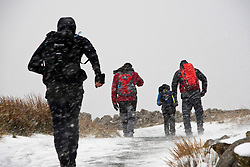 © Licensed to London News Pictures. 06/04/2021. Llanberis, Conwy, Wales, UK.People head off up the track for Mount Snowdonin a blizzard at Pen-Y-Pass as snow and hail hit Snowdonia National Park, in Conwy, Wales, UK. Photo credit: Graham M. Lawrence/LNP
