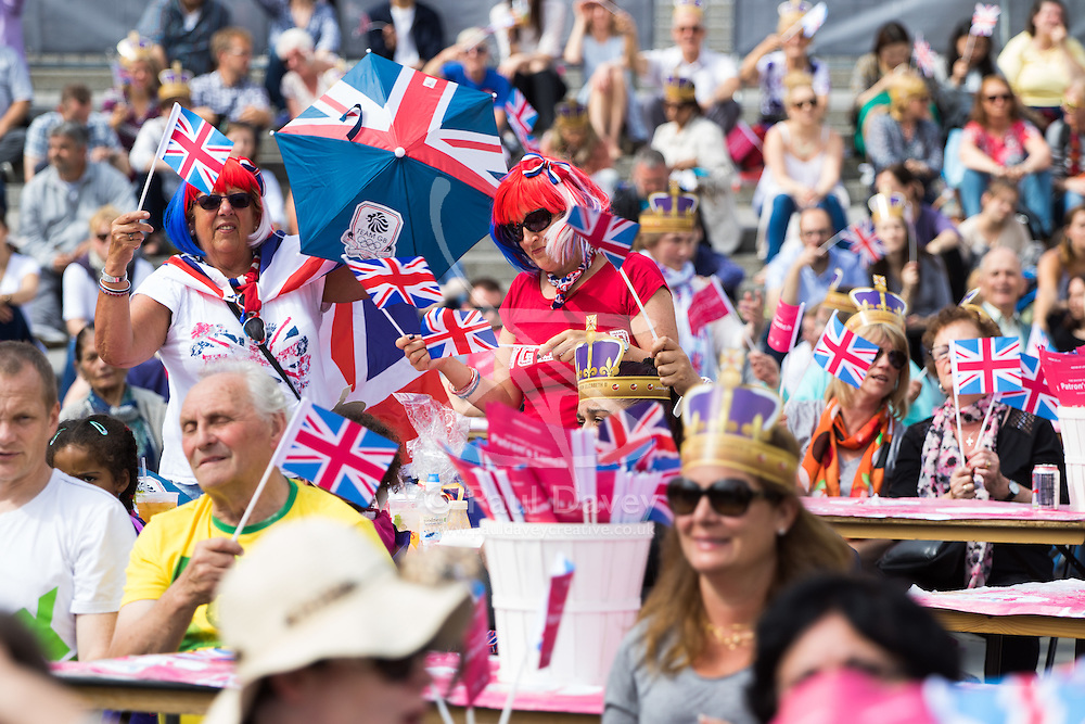 Trafalgar Square, London, June 12th 2016. Rain greets Londoners and visitors to the capital's Trafalgar Square as the Mayor hosts a Patron's Lunch in celebration of The Queen's 90th birthday. PICTURED: Flag-waving men and women enjoy the atmosphere.
