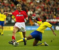Photo. Chris Ratcliffe<br />Charlton v Arsenal. FA Premiership. 26/10/2003<br />Ashley Cole tackles Jonatan Johansson at the Valley durng the 1-1 draw.