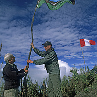 Cordillera Vilcabamba, Andes Mountains, Peru. Peter Frost and Scott Gorsuch raise National Geographic flag at base camp for archaeological expedition to Cerro Victoria.