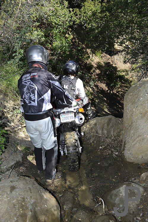 Bill Dragoo helping Val (women rider) descend steep slope during pit competition at 2010 Rawhyde Adventure Rider Challenge