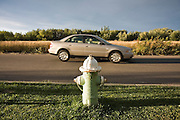 A car drives past a fire hydrant in Boulder, Colorado. The green lawn below the hydrant is in sharp contrast to the dry, browned grasses in the open space across the street.