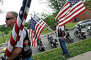 Members of the Patriot Guard Riders holding US flags prior to the funeral service of Sgt. Ian T. Sanchez, in Staten Island, NY., on Tuesday, June 27, 2006. Sgt. Sanchez, a 26-year-old American serviceman was killed by a roadside bomb in the Pech River Valley, Afghanistan. The Patriot Guard Riders is a diverse amalgamation of riders from across the United States of America. Besides a passion for motorcycling, they all have in common an unwavering respect for those who risk their lives for the country's freedom and security. They are an American patriotic group, mainly but not only, composed by veterans from all over the United States. They work in unison, calling upon tens of different motorcycle groups, connected by an internet-based web where each of them can find out where and when a 'Mission' is called upon, and have the chance to take part. This way, the Patriot Guard Riders can cover the whole of the United States without having to ride from town to town but, by organising into different State Groups, each with its own State Captain, they are still able to maintain strictly firm guidelines, and to honour the same basic principles that moves the group from the its inception. The main aim of the Patriot Guard Riders is to attend the funeral services of fallen American servicemen, defined as 'Heroes' by the group,  as invited guests of the family. These so-called 'Missions' they undertake have two basic objectives in particular: to show their sincere respect for the US 'Fallen Heroes', their families, and their communities, and to shield the mourners from interruptions created by any group of protestors. Additionally the Patriot Guard Riders provide support to the veteran community and their families, in collaboration with the other veteran service organizations already working in the field.   **ITALY OUT**