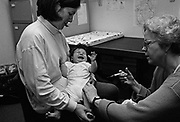 """Diptheria, tetanus, polio, whooping cough, meningitis.""  A four month-old baby screams with the sharp prick of an innoculation needle administered by a health visitor at a doctor's surgery, London. The post-natal clinic is a health check for the baby and for new mothers to discuss parenting problems with a NHS-qualified midwife and paediatric specialist. She attends to mother and child since they arrived back home from hospital, days after birth and therefore knows all their details and the baby's growth statistics and development curves. This is from a documentary series of pictures about the first year of the photographer's first child Ella. Accompanied by personal reflections and references from various nursery rhymes, this work describes his wife Lynda's journey from expectant to actual motherhood and for Ella - from new-born to one year-old."