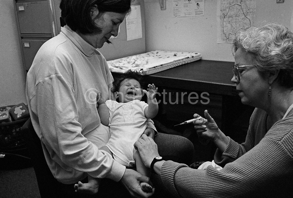 """""""Diptheria, tetanus, polio, whooping cough, meningitis.""""  A four month-old baby screams with the sharp prick of an innoculation needle administered by a health visitor at a doctor's surgery, London. The post-natal clinic is a health check for the baby and for new mothers to discuss parenting problems with a NHS-qualified midwife and paediatric specialist. She attends to mother and child since they arrived back home from hospital, days after birth and therefore knows all their details and the baby's growth statistics and development curves. This is from a documentary series of pictures about the first year of the photographer's first child Ella. Accompanied by personal reflections and references from various nursery rhymes, this work describes his wife Lynda's journey from expectant to actual motherhood and for Ella - from new-born to one year-old."""