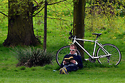 © Licensed to London News Pictures. 06/05/2013. London, UK A man reads a book under the shade of a tree in Hyde Park. People enjoy the sunny bank holiday Monday weather today 6th May 2013 in London's Royal Parks. Photo credit : Stephen Simpson/LNP