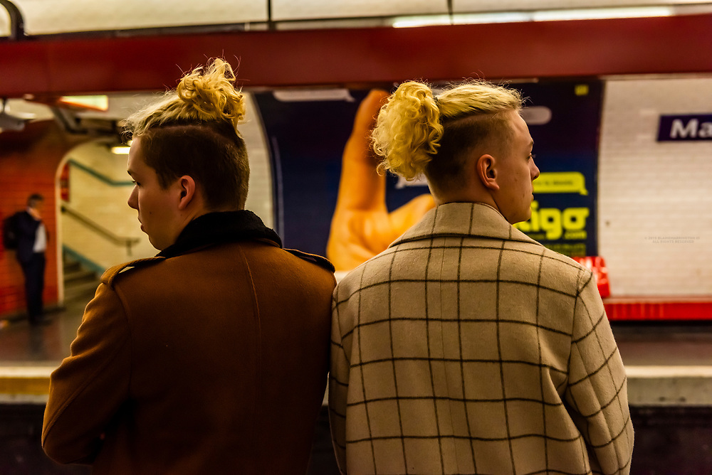 Young French men waiting for a Metro train, Paris, France.
