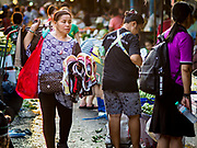 "04 DECEMBER 2018 - BANGKOK, THAILAND:  A woman selling women's underwear carries her merchandise in her hands in a plastic bag. The issue of plastic waste became a public one in early June when a whale in Thai waters died after ingesting 18 pounds of plastic. In a recent report, Ocean Conservancy claimed that Thailand, China, Indonesia, the Philippines, and Vietnam were responsible for as much as 60 percent of the plastic waste in the world's oceans. Khlong Toey (also called Khlong Toei) Market is one of the largest ""wet markets"" in Thailand. The market is located in the midst of one of Bangkok's largest slum areas and close to the city's original deep water port. Thousands of people live in the neighboring slum area. Thousands more shop in the sprawling market for fresh fruits and vegetables as well meat, fish and poultry.     PHOTO BY JACK KURTZ"