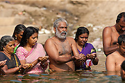Indian Hindu men and women bathing and praying in the River Ganges by Kshameshwar Ghat in holy city of Varanasi, India