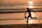 A young man chases after a soccer ball on the beach in Seminyak, Bali