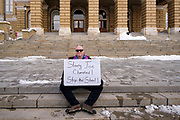"""02 JANUARY 2021 - DES MOINES, IOWA: A supporter of President Donald Trump sits on the front steps of the Iowa State Capitol. About 30 people marched around the Iowa State Capitol Saturday afternoon to protest the outcome of the November 3 general election in the United States. They are a part of the """"Stop the Steal"""" movement which maintains that the election was stolen from Donald Trump by massive voter fraud. There is no evidence supporting their conspiracy theory. This is the 9th week Donald Trump supporters have marched around the Capitol. They've been there every week since the Nov. 3 election. More than 1,000 people showed up the first week, but the crowd has gotten smaller every week.     PHOTO BY JACK KURTZ"""