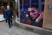 Photograph of a womans head with staring eyes makes an interesting street scene as a man interacts unbeknown on New Bond Street, London, United Kingdom. A weird visual juxtaposition is created as people integrate with the large scale window display.