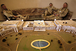 Soldiers rest in inside Saddam Hussein's Presidential Palace, while sitting in front of a model of it, Baghdad, Iraq, Sept. 29, 2003.