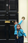 © Licensed to London News Pictures. 03/06/2012. London, UK. Two girls play with number 11's doorbell. The UK Prime Minister hosts a street party on Downing Street today. The party was moved inside number 10 due to the weather but the PM came onto the street to play games with the children who had gathered.  The Royal Jubilee celebrations. Great Britain is celebrating the 60th  anniversary of the countries Monarch HRH Queen Elizabeth II accession to the throne this weekend Photo credit : Stephen Simpson/LNP