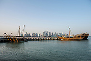 Dhows are tied up to a dock in Doha, Qatar. The city's modern skyline is seen beyond these traditional boats.