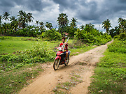 21 JUNE 2016 - DON KHONE, CHAMPASAK, LAOS: A man carries bamboo poles on his motorbike in the countryside on Don Khone Island. Don Khone Island, one of the larger islands in the 4,000 Islands chain on the Mekong River in southern Laos. The island has become a backpacker hot spot, there are lots of guest houses and small restaurants on the north end of the island.       PHOTO BY JACK KURTZ