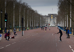 © Licensed to London News Pictures. 21/02/2021. London, UK. A man and his son (L) play a quick game of tennis in a nearly deserted Mall in sight of Buckingham Palace in central London. Temperatures reached 14 C in parts of the south today. Photo credit: Peter Macdiarmid/LNP