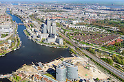Nederland, Noord-Holland, Amsterdam, 09-04-2014; Omval met Rembrandt, Mondriaan en Breitner torens langs rivier de Amstel. Hoofdkantoor Philips in de Breitner toren en daarnaast Delta Lloyd, vormt het begin van de Zuid-as en achter de kantoortorens het Amstelstation, Aan het water stadsvilla's en woonboten. Links kantoorgebouw Rivierstaete aan de President Kennedylaan ('de Apenrots') <br /> Rembrandt, Mondriaan and Breitner towers along the Amstel River. Headquarter Philips in the Breitner tower as well as Delta Lloyd<br /> The complex marks the beginning of the South axis ('city' - financial district). Behind the office towers the river Amstel with water villas and houseboats, in earlier times was this an industrial area<br /> luchtfoto (toeslag op standard tarieven);<br /> aerial photo (additional fee required);<br /> copyright foto/photo Siebe Swart