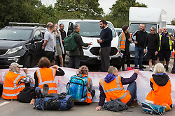Enfield, UK. 15th September, 2021. Insulate Britain climate activists block a slip road from the M25 at Junction 25 as part of a campaign intended to push the UK government to make significant legislative change to start lowering emissions. The activists, who wrote to Prime Minister Boris Johnson on 13th August, are demanding that the government immediately promises both to fully fund and ensure the insulation of all social housing in Britain by 2025 and to produce within four months a legally binding national plan to fully fund and ensure the full low-energy and low-carbon whole-house retrofit, with no externalised costs, of all homes in Britain by 2030 as part of a just transition to full decarbonisation of all parts of society and the economy.