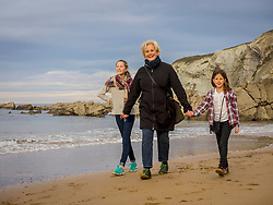 Grandmother walking with girls on beach