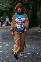 © Licensed to London News Pictures. 03/10/2021. London, UK. A runner dressed as a lion arrives in Greenwich Park ahead of the start of the London Marathon.This London Marathon will be the first full scale staging of the race in more than two years due to the Coronavirus Pandemic.  Photo credit: George Cracknell Wright/LNP