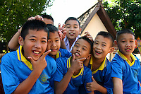 """Thai Schoolboys mugging and smiling for the camera. Schools are often found within temple compounds in Thailand, and in fact are local centers of each neighborhood serving as a kind of """"community center""""."""