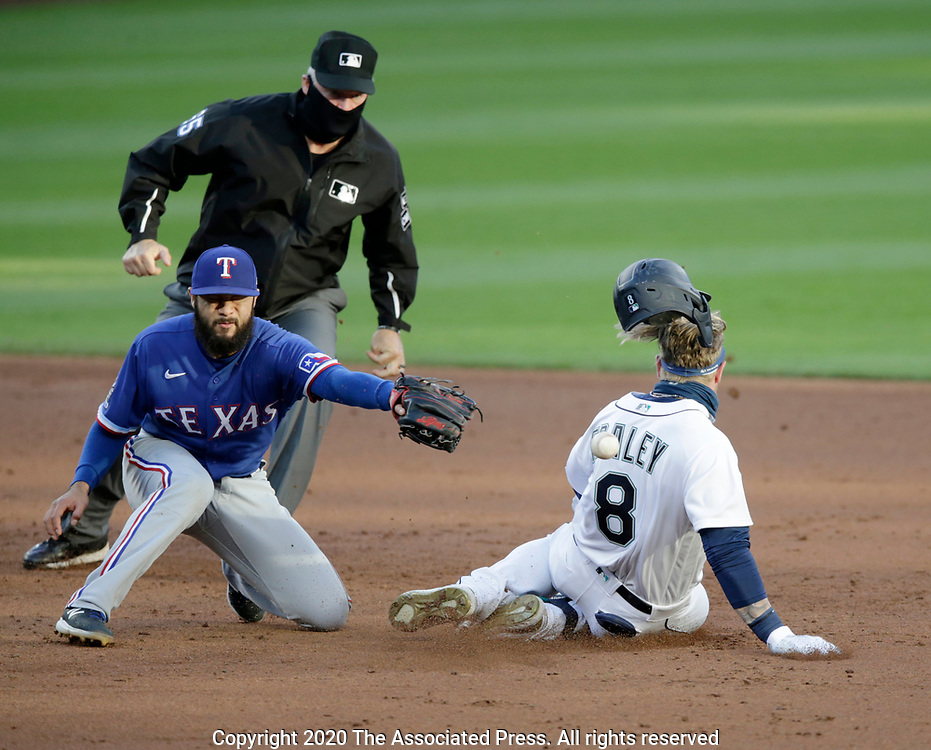 Seattle Mariners' Jake Fraley loses his batting helmet while sliding safely into second for a double as Texas Rangers short stop Isiah Kiner-Falefa reaches for the ball during the third inning of a baseball game, Saturday, Aug. 22, 2020, in Seattle. (AP Photo/John Froschauer)
