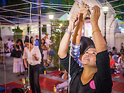 """31 DECEMBER 2012 - BANGKOK, THAILAND: Women tie New Year's blessing to a string at Wat Pathum Wan next to Central World in Bangkok. Many Thais go to Buddhist temples and shrines to """"make merit"""" for the New Year. The traditional Thai New Year is based on the lunar calender and is celebrated in April, but the Gregorian New Year is celebrated throughout the Kingdom, especially in larger cities and tourist centers, like Bangkok, Chiang Mai and Phuket. The Bangkok Countdown 2013 event was called ?Happiness is all Around @ Ratchaprasong.? All of the streets leading to Ratchaprasong Intersection were closed and the malls in the area stayed open throughout the evening.    PHOTO BY JACK KURTZ"""