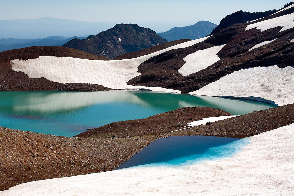 A melting glacier on Broken Top peak forms a small ice-blue lake on the flank of the mountain.