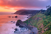 Red and yellow sky above blurred water seen at overlook site at Ecola in Oregon. Green cliffs