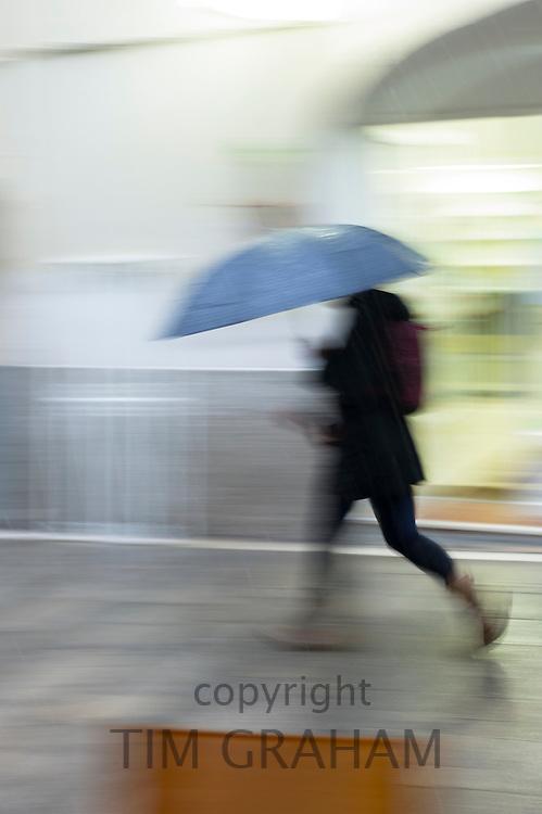 Person walking with umbrella in rainy day scene in Kerkyra, Corfu Town, Greece