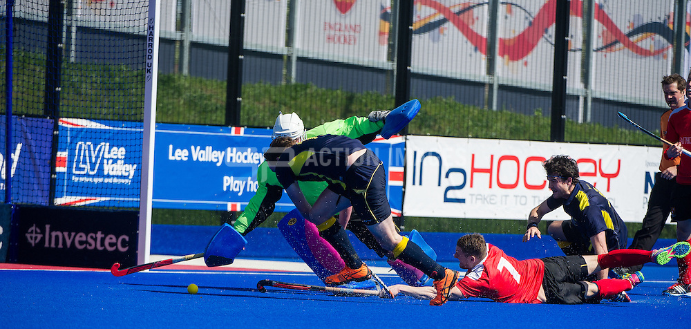 Holcombe's Gareth Andrews tries to touch the ball past Tom Skinner in the Team Bath Buccaneers goal. Holcombe v Team Bath Buccaneers - Now: Pensions Finals Weekend, Lee Valley Hockey & Tennis Centre, London, UK on 12 April 2015. Photo: Simon Parker
