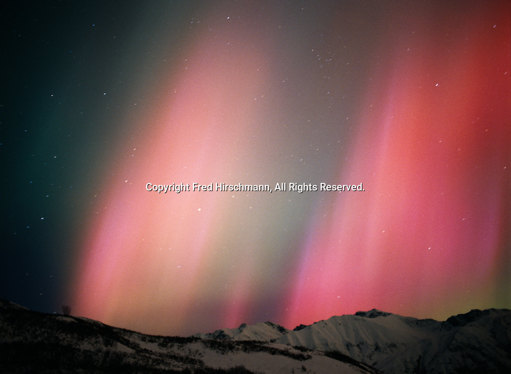 Pink aurora above Arkose Ridge of the Talkeetna Mountains during geomagnetic storm on the morning of November 24, 2001, Little Susitna River Valley, Alaska.