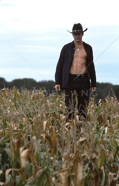 cowboy with an open shirt standing in a cornfield