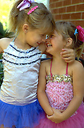 Sisters affectionately smiling at each other in dance costumes age 4 and 3.  WesternSprings Illinois USA