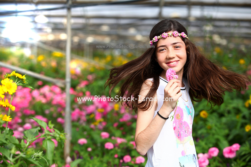 Young preteen girl of 12 in white dress in a hothouse of pink flowers