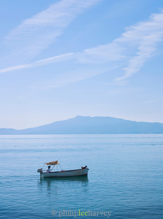 A small fishing boat sails across the calm blue waters of the Mediterranean Sea at Talamone in Tuscany, Italy