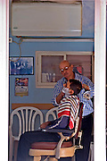 Israel, Tel Aviv, Jaffa, old style barber in his shop shaving a customer