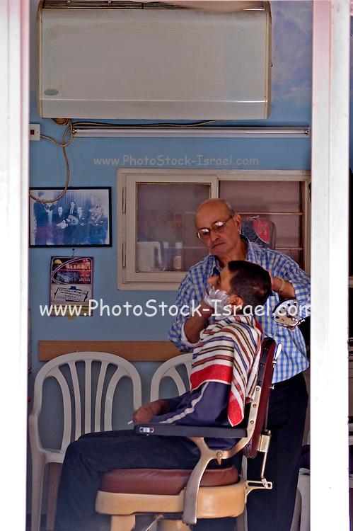 Israel, Tel Aviv, Jaffa, old style barber in his shop shaving a customer