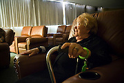 Resident Miriam Zolten Fleisher relaxes on a leather sofa in the media room at the old-age home Paseo de Valencia in Laguna HIlls, California.