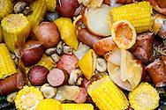 Some good ole' fixings from a shrimp boil. It has sausage, corn, mushrooms, onions, lemons, cayenne, potato.