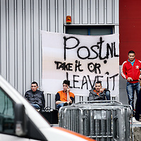 Nederland, amsterdam , 26 juni 2013.<br /> Stakende Bezorgers van PostNL voor een spandoek met de leuze PostNL take it or leaver it voor de Post.NL distributielocatie aan Jarmuiden.<br /> Foto:Jean-Pierre Jans