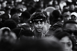 London, August 29th 2016. A young man from the crowd on Ladbroke Grove, picked out from a distance, appears to look into the camera during day two of Europe's biggest street party, the Notting Hill Carnival.