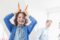Portrait of girl making devil with carrots as horns, smiling