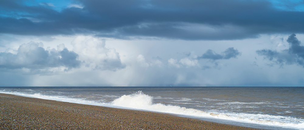 Shoreline, shingle pebble beach and breaking waves under blue sky and puffy dark clouds in wintertime at Cley Next The Sea, Norfolk, UK
