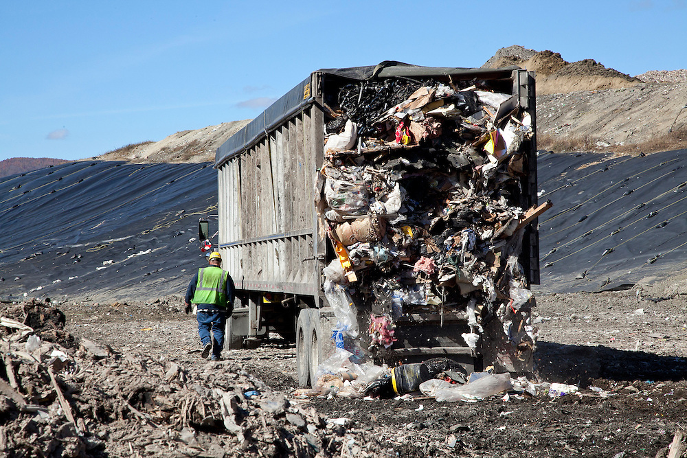 Municipal Solid waste transfer truck dumps load in open cell of sanitary landfill