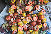 Low Country Boil by Rodney Bedsole, a food photographer based in Nashville and New York City. Shrimp, sausage, potatoes, and corn on the cob on a newspaper.